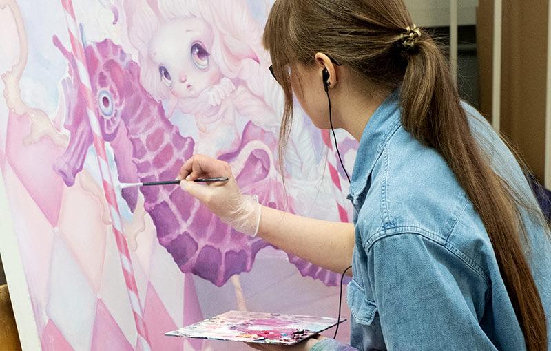 Opiskelija maalaamassa kuvataiteen oppitunnilla