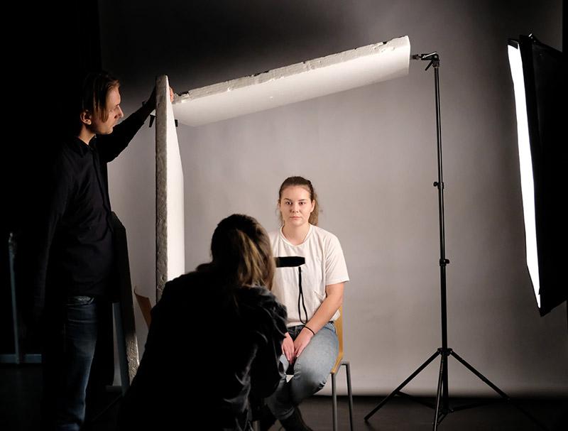 Opiskelijat ottamassa valokuvia studiossa