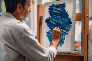 Kuvituskuvassa mies maalaa maalaustelineessä olevalle paperille abstraktia sinistä kuviota.